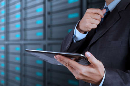 data backup: businessman hand using tablet computer and server room background Stock Photo