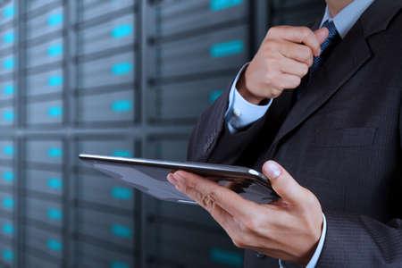 businessman hand using tablet computer and server room background Imagens