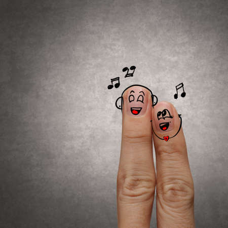 A happy finger couple in love with painted smiley and sing a song photo