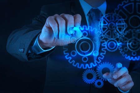 ingenieria industrial: mano de hombre de negocios saca engranaje al concepto de �xito en la computadora de pantalla t�ctil Foto de archivo