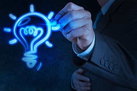 businessman hand with a pen drawing light bulb on touch screen photo