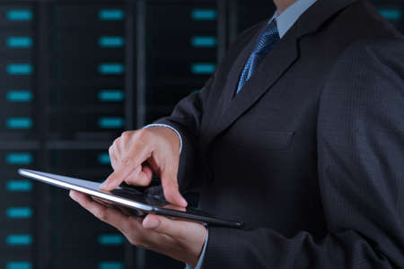 business solutions: businessman hand using tablet computer and server room background Stock Photo