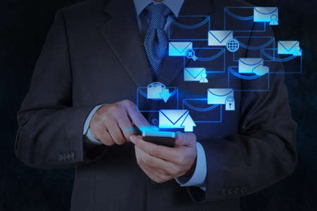 got: businessman hand use smart phone computer with modern email icon