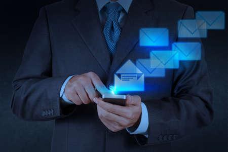 empres�rio lado o uso do computador telefone inteligente com o �cone de e-mail Banco de Imagens
