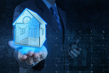 businessman hand shows house model as concept photo