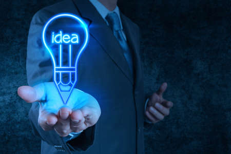 businessman hand shows pen light bulb on touch screen as creative concept photo