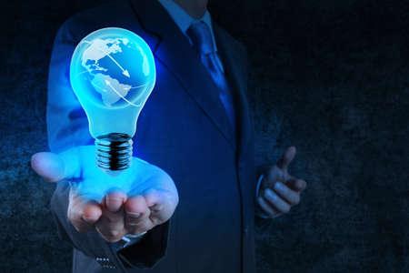 Geschäftsmann Hand zeigt Glühlampe mit Erde sozialen Netzwerk als Konzept