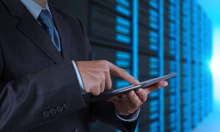 service center: businessman hand using tablet computer and server room background Stock Photo