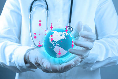 link: Medical Doctor holding a world globe in his hands as medical network as concept Stock Photo