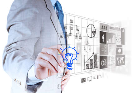 strategy diagram: businessman hand draws lightbulb with new computer interface as solution business concept