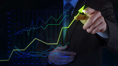 market trends: businessman hand drawing virtual chart business on touch screen computer as concept