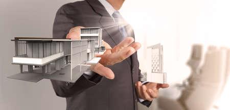 businessman hand presents house model on modern computer as delvelopment concept Stock Photo - 19646795