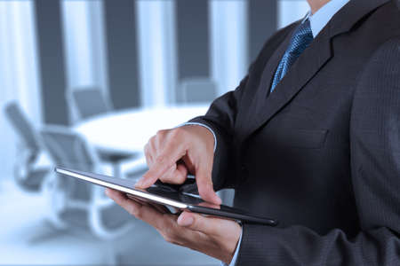 input devices: Businessman hand working with a digital tablet on meeting room background