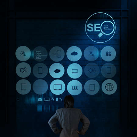 website words: businessman hand showing search engine optimization SEO as concept