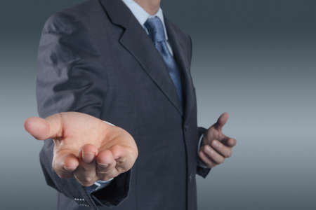 reaching:  business man with an open hand as showing something concept