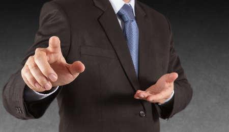 Businessman hand pressing an imaginary button on virtual screen Stock Photo
