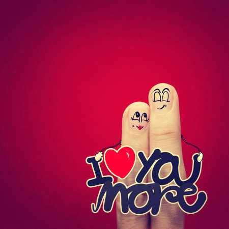 the happy vintage  finger couple in love with painted smiley and hold word love you more photo