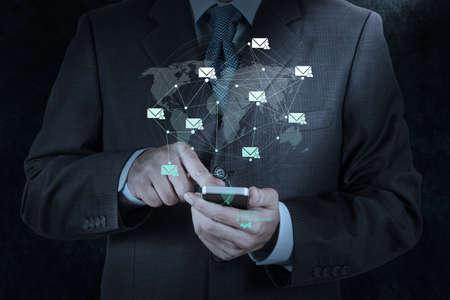 touchscreen: la mano de negocios el uso de computadoras de tel?fonos inteligentes con el icono de correo electr?nico como concepto