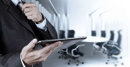 Businessman hand working with a digital tablet on meeting room background Stock Photo - 20101066