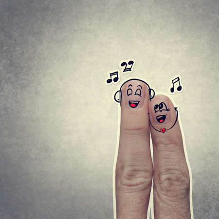 the happy finger couple in love with painted smiley and sing a song photo