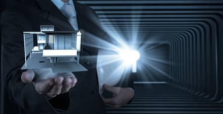 businessman hand presents house model on modern computer as development concept Reklamní fotografie