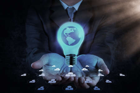 Businessman hand shows Light bulb with planet Earth as concept photo