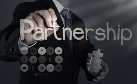 businessman hand shows light and puzzle partnership photo