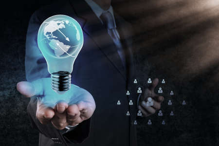 Businessman hand shows Light bulb with planet Earth social network as concept photo