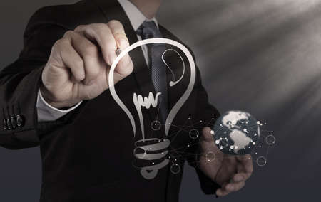 businessman hand with a pen drawing light bulb photo