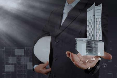 businessman hand presents building development as concept photo