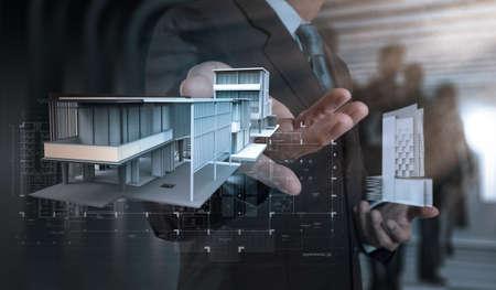 사업가 손은 개발 개념으로 현대 컴퓨터에 집 모델을 제시 스톡 콘텐츠