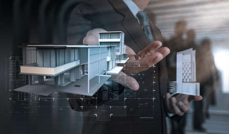 architecture model: businessman hand presents house model on modern computer as development concept Stock Photo