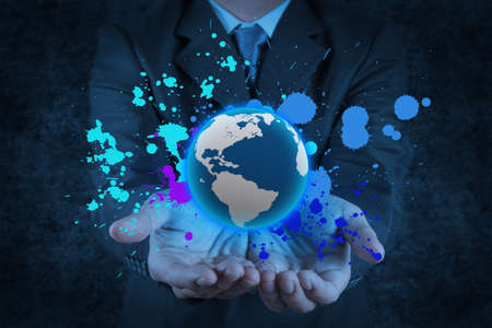 businessman holding a glowing earth globe in his hands and splash colors as concept photo