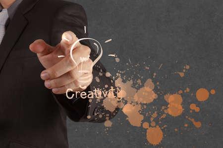 pensamiento creativo: mano de hombre de negocios saca bombilla con interfaz de la computadora como nuevo concepto de la soluci?n de negocio Foto de archivo