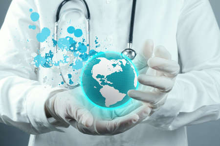 Doctor Holding  World Globe and splash colors In Her Hands, Concept Of World Health photo