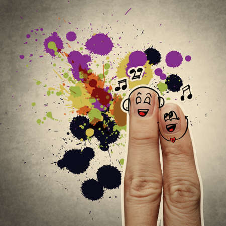 the happy finger couple in love with painted smiley and sing a song on splash colors background photo