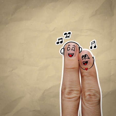 the happy finger couple in love with painted smiley and sing a song on recycle background photo