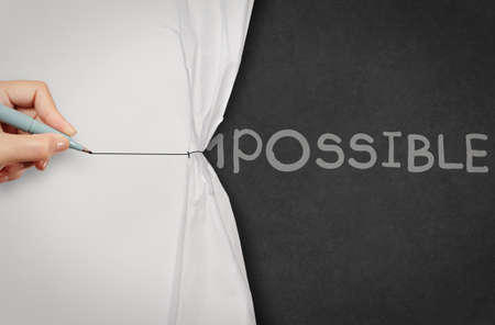 possibility: hand pull wrinkled paper show word impossible transformed into possible as concept Stock Photo