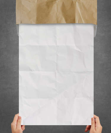 hand pulling crumpled paper from recycle envelope as concept background photo