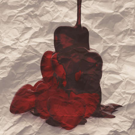 syrupy: chocolate syrup leaking over heart shape symbol on crumpled paper Stock Photo
