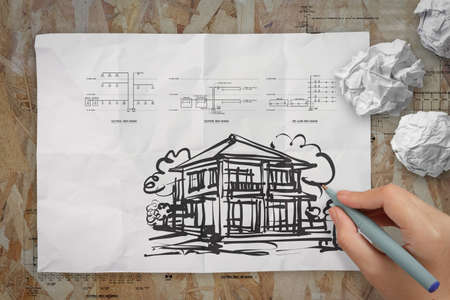 hand drawing house on wrinkled paper as concept photo