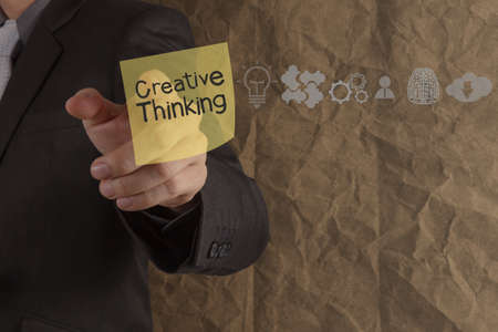businessman hand point creative thinking on sticky note with icons crumpled recycle paper background as concept photo