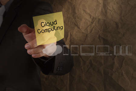 businessman hand point cloud computing on sticky note with icons crumpled recycle paper background as concept photo