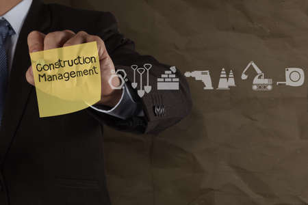 businessman hand point construction management on sticky note and icons with crumpled paper background as concept Stock Photo - 22852323