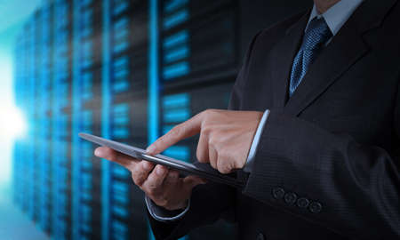 タブレット コンピューターとサーバー ルームの背景を使用して実業家の手