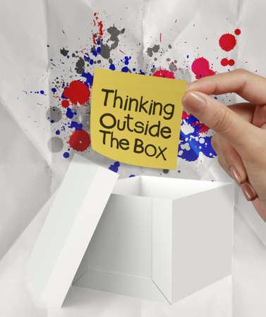 think out of the box: hand hold sticky note thinking outside the box and splash colors crumpled paper as concept