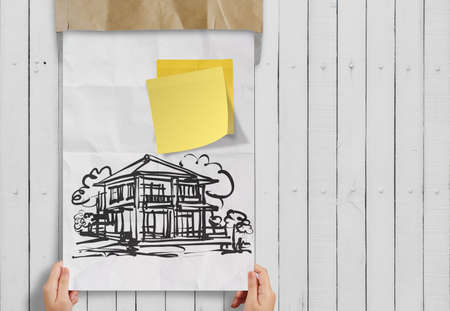 smart investment  sticky note with house crumpled envelope paper as concept photo