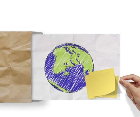 blank sticky note and sketch illustration of planet earth on crumpled envelope paper background as concept illustration