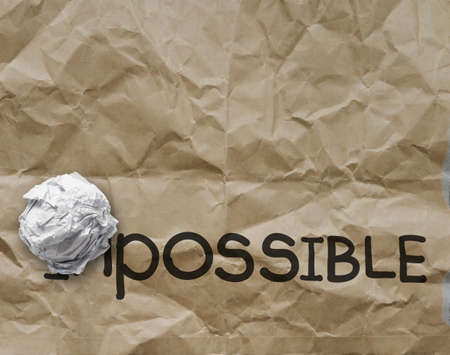 possibility: crumpled paper through word impossible transformed into possible as concept Stock Photo