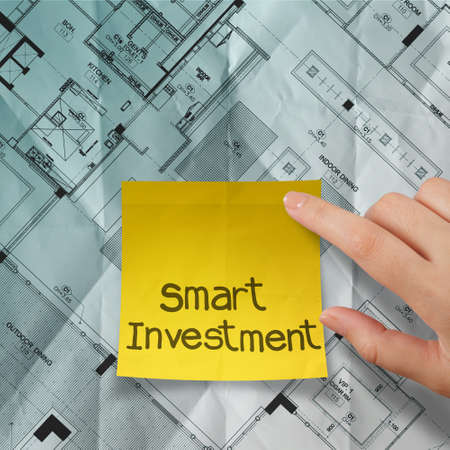 hand point smart investment sticky note with crumpled blue print part of architectural project photo